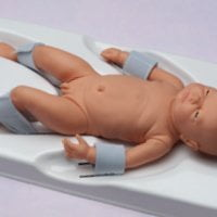 A doll of a baby boy in a circumstraint showing how he would be restrained for his surgery
